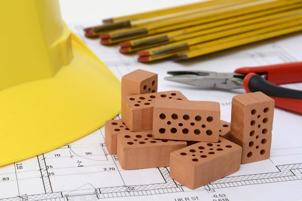 Baumaterial liegt auf den Planungsunterlagen eines Hausneubaus.