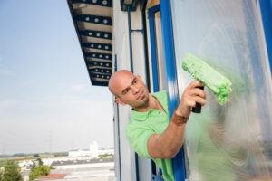 Gebäudereiniger reinigt Glasfassade.