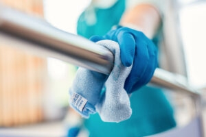 Reinigungskraft reinigt Edelstahlstange.